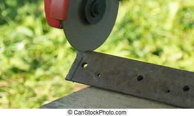 Man peel a metal corner by grinder - man sawing metal by...