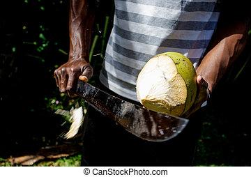 Man peeling a coconut