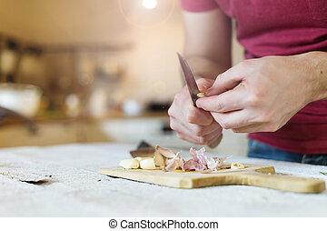 Man peeling garlic - Unrecognizable man in the kitchen...
