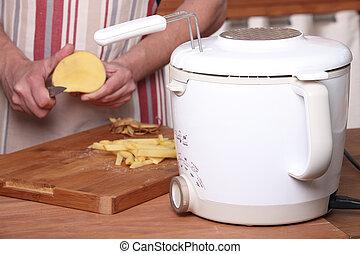 Man peeling potatoes to make French fries