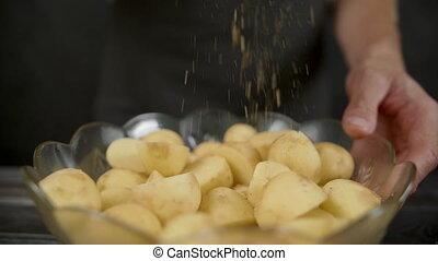 Man pepper potato in the dark kitchen.