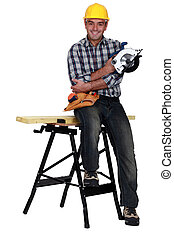 Man perched on work bench