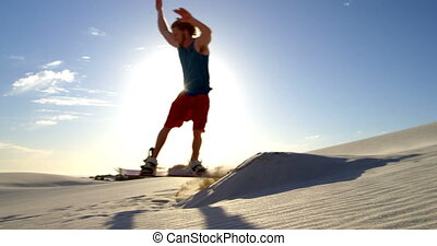 Man performing a jump while sand boarding 4k - Man...