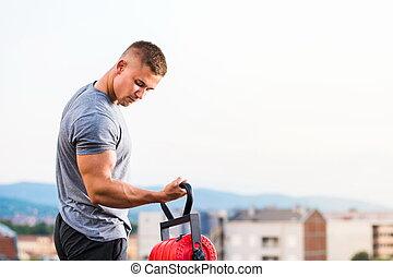 Man performing biceps workout at rooftop - Man performing ...