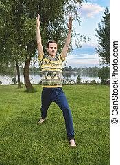 Man performing yoga young fitness man outdoor doing exercise. leg stretch
