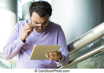 Man perplexed by what he sees on tablet - Closeup portrait,...