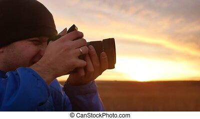 man photographer in nature holds a camera takes pictures -...