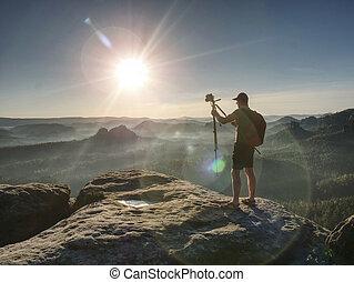 Man photographer taking photo on sunset mountain peak