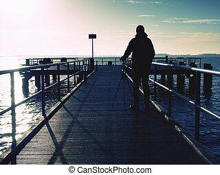 Man, photographer taking photos at lake at sunset. Hobby photographer on vacation.