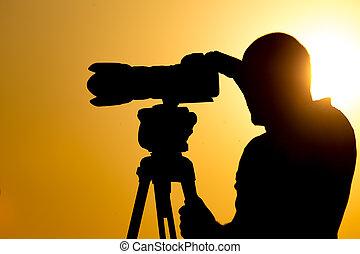 Man photographer with a camera at sunset