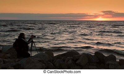 Man photographing beautiful sunset at seaside