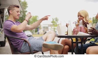 man photographing friends eating at food truck - leisure,...