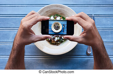 Man photographing his delicious salad at a blue bistro table...