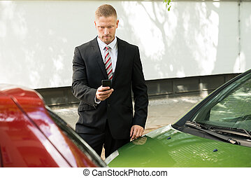 Man Photographing His Vehicle After Traffic Collision