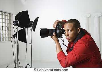 Man photographing in studio. - African American young male ...