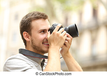 Man photographing with a camera in the street