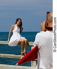 man photographs the girl on the bridge