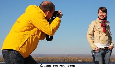 man photographs woman on nature against the river, wood and an clear sky