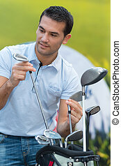 man picking his golf club