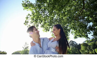 Man picking up his pretty girlfriend in the park on a sunny...
