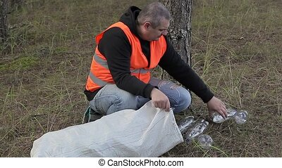 Man picking up used plastic bottles in forest