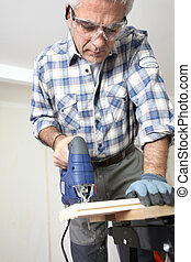 Man piercing a hole through a wooden plank