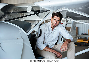 Man pilot sitting in small airplane
