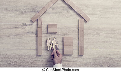Man placing a cut out of his family inside a wood frame home in a concept of home ownership