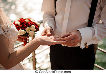 Man placing a ring on the his fiancee finger standing on the pier on the lake