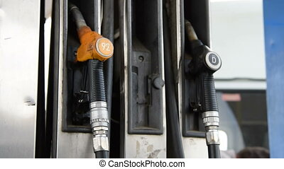 Man placing fueling nozzle on holder - Man fixing fueling...
