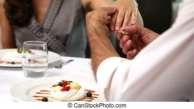 Man placing ring on new fiances finger at a restaurant