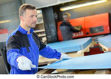 Man placing sheetmetal onto a pallet