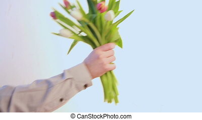 Man placing tulips in vase - Man wearing shirt placing...