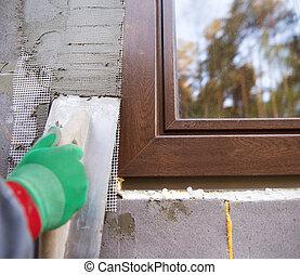 Man plastering - Plasterer spreading out plaster with trowel...
