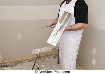 Man plastering wall with work tools