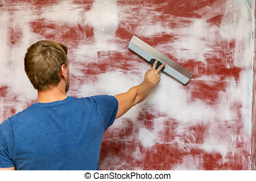 man plastering wall with taping knife