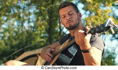 Man play guitar at forest - Young man travel with guitar in...
