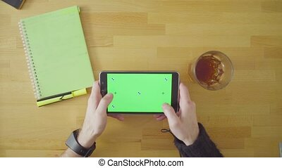 Man playing a game on tablet with green screen