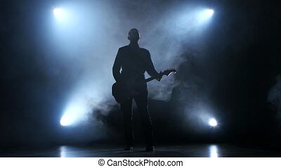 Man playing a slow tune on the guitar. Smoke studio