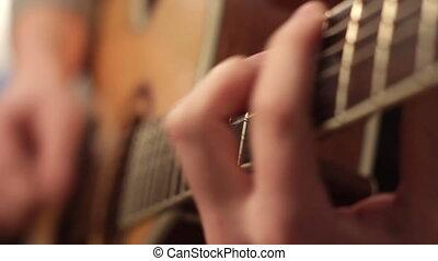 man playing acoustic guitar close up
