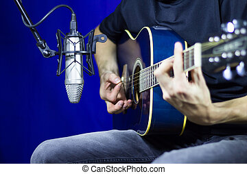 Man playing acoustic guitar in front of a microphone