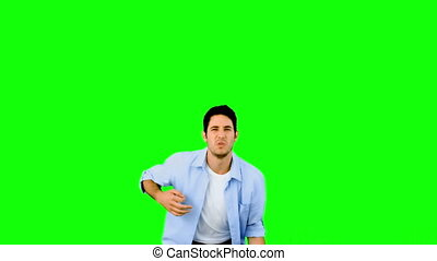 Man playing air guitar on green screen in slow motion