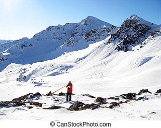Man playing alpenhorn in mountains near Scuol, Switzerland