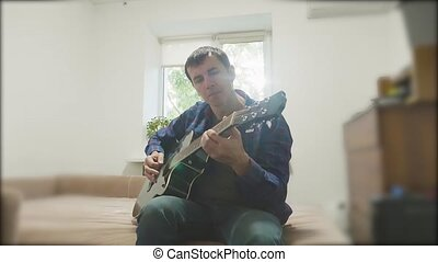Man playing an acoustic guitar. Man Playing Acoustic Guitar Close Up lifestyle slow motion video. in the room sits on the couch. man and guitar concept
