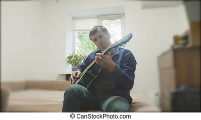 Man playing an acoustic guitar. Man Playing Acoustic Guitar Close Up slow motion video. in the room sits on the couch lifestyle. man and guitar concept