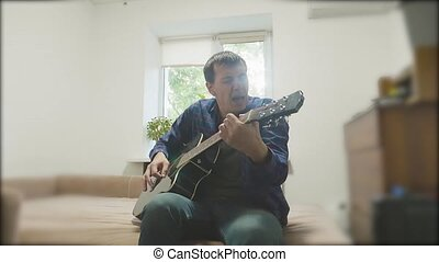 Man playing an acoustic guitar. Man Playing Acoustic Guitar Close Up slow motion video. in the room sits on the couch. man and lifestyle guitar concept