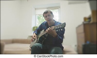 Man playing an acoustic guitar. Man Playing Acoustic Guitar Close Up slow motion video. in the room sits on the couch. man lifestyle and guitar concept