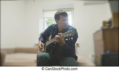 Man playing an acoustic guitar. Man Playing Acoustic Guitar Close Up slow motion video. in the room sits on the couch. man and guitar concept lifestyle