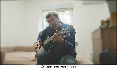 Man playing an acoustic guitar. Man Playing Acoustic Guitar Close Up slow motion video. lifestyle in the room sits on the couch. man and guitar concept