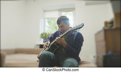 Man playing an acoustic guitar. Man Playing Acoustic Guitar Close Up slow motion video lifestyle. in the room sits on the couch. man and guitar concept
